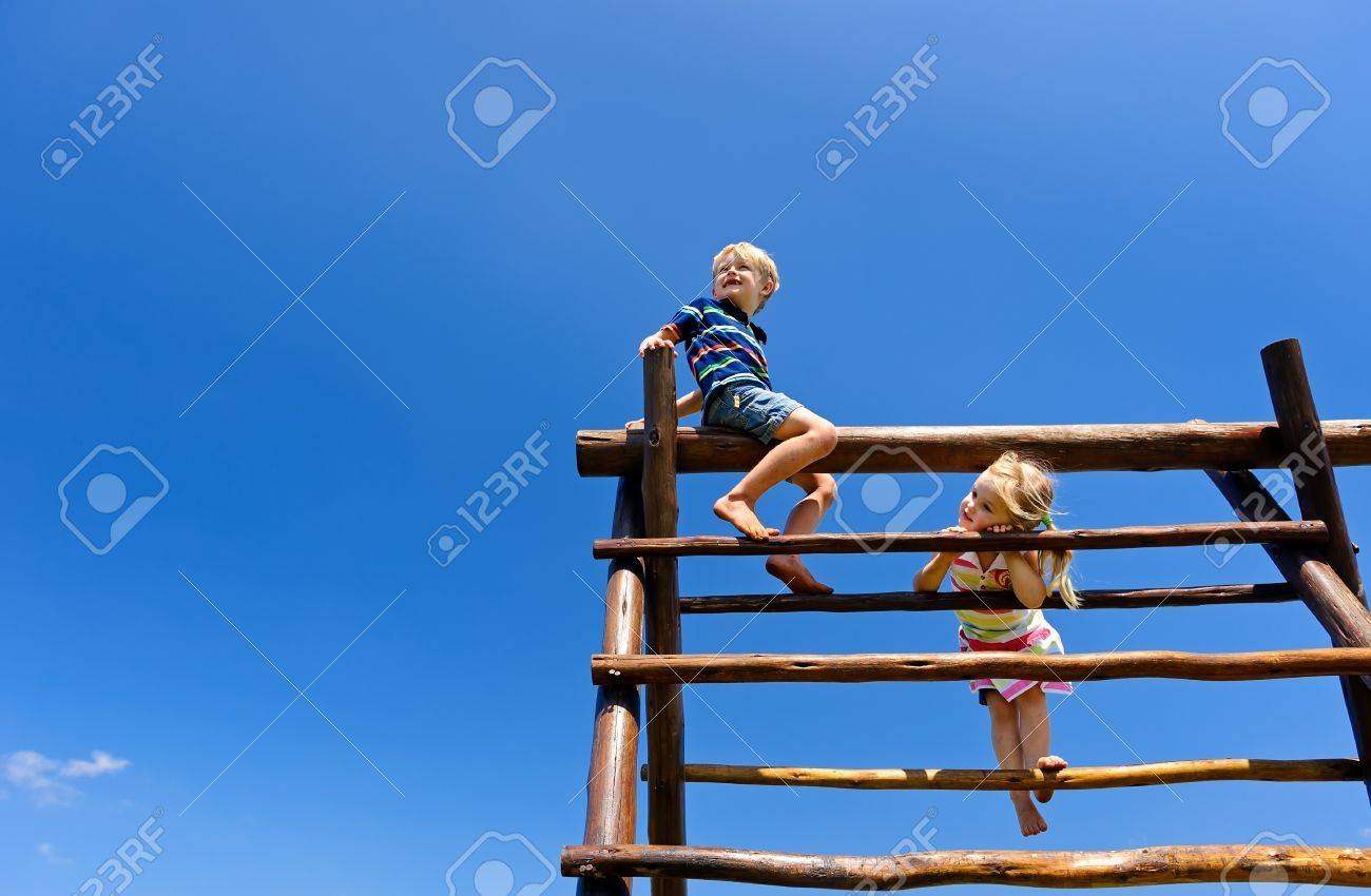 Two young children sitting at the top of playground equipment Stock Photo - 8726896