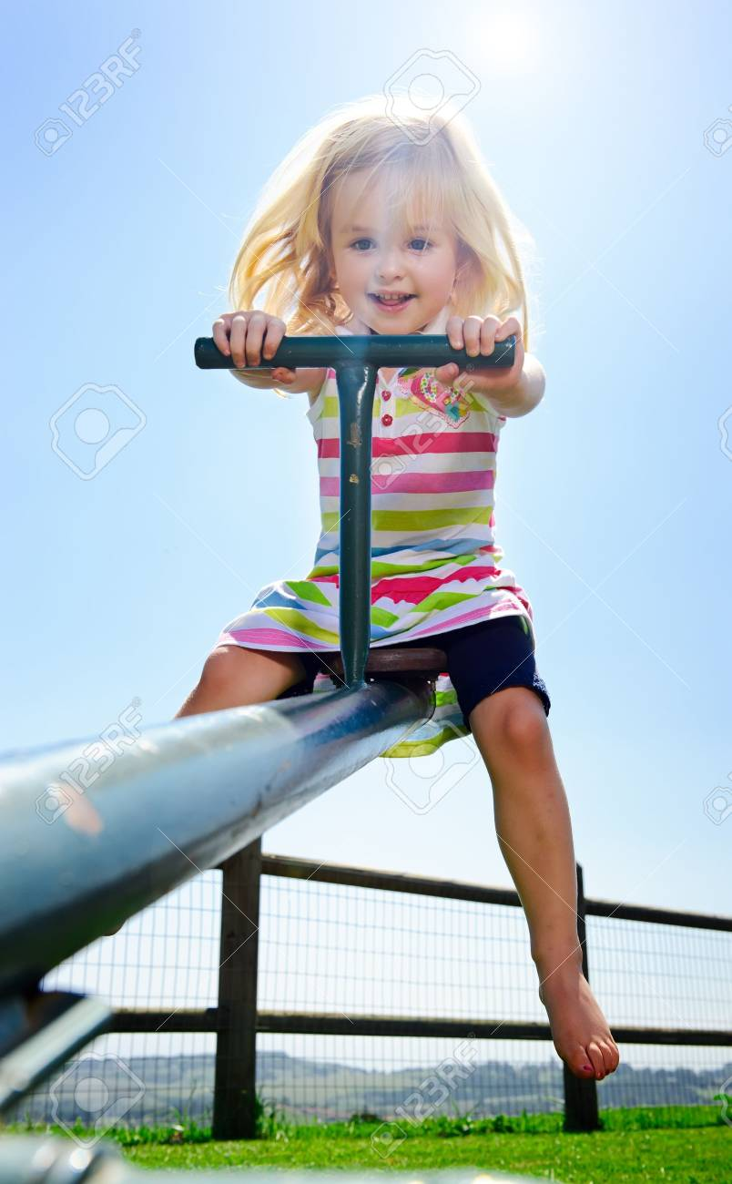 Young child playing with the seesaw at the playground Stock Photo - 8726822
