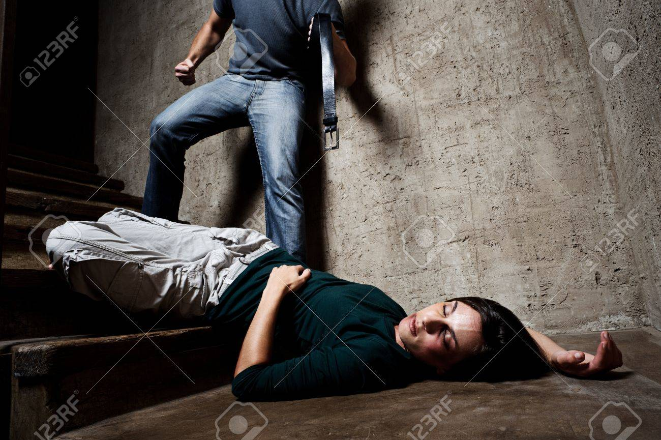 Battered woman lies lifelessly at the bottom of stairs with a faceless man holding a belt, a conceptual shoot portraying the process and effects of domestic violence Stock Photo - 8726433