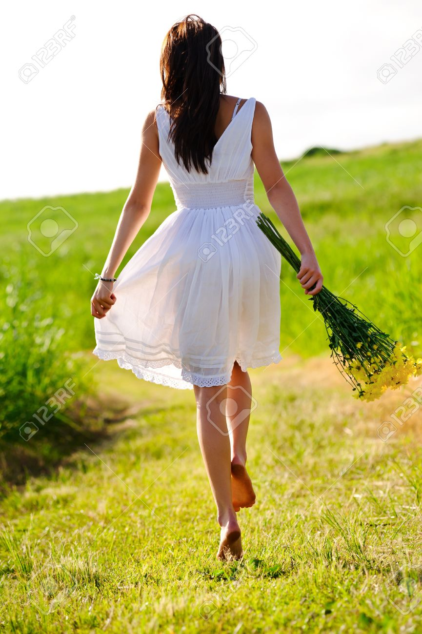 White dress skipping girl in field with flowers at sunset Stock Photo - 8726283