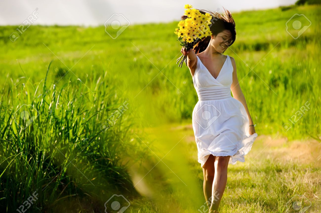 Candid skipping carefree adorable woman in field with flowers at summer sunset. Stock Photo - 8726276