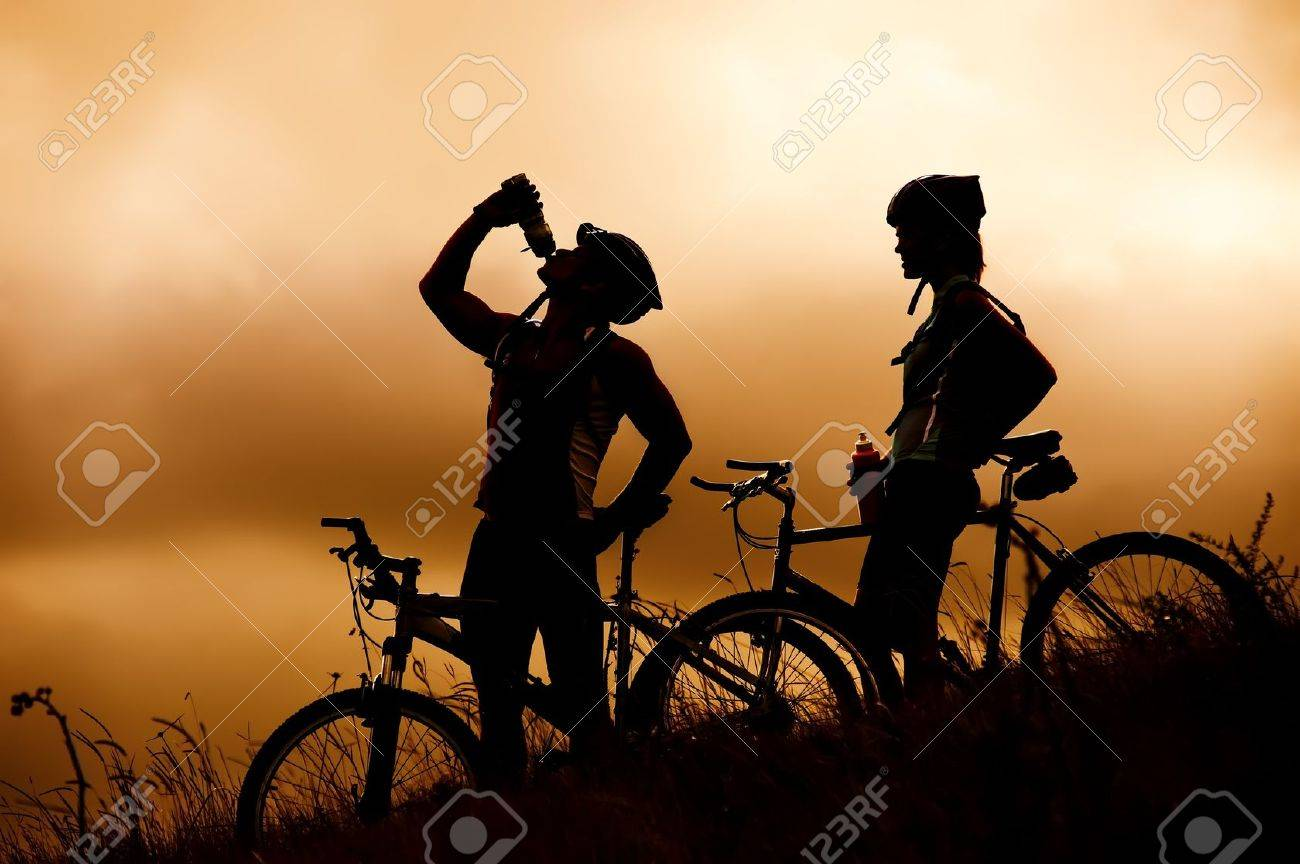 Attractive, healthy couple drink from their water bottles on mountain bikes. active outdoor lifestyle concept Stock Photo - 8921619