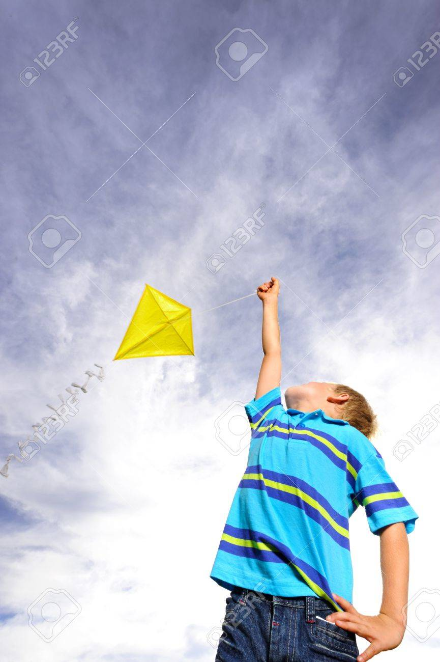 Young boy flies a yellow kite on a windy summer day - 9967819