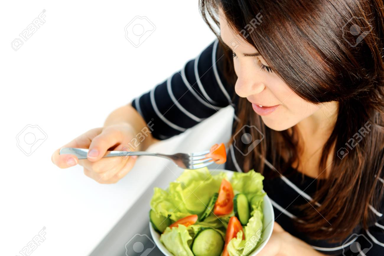 Beautiful brunette is eating a healthy green salad Stock Photo - 10803057