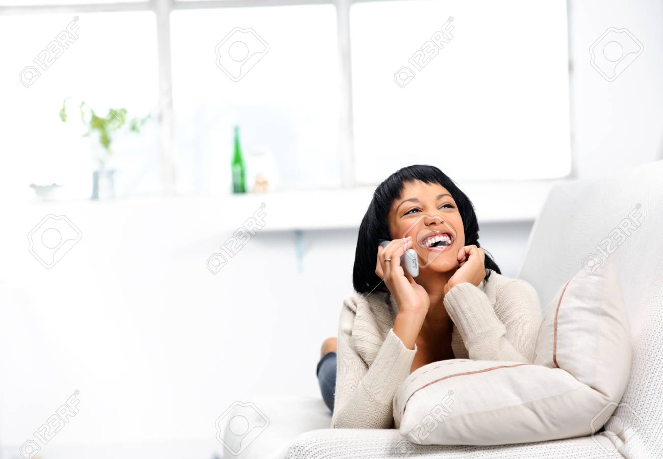 Cute indian girl laughing on the couch while on the telephone Stock Photo - 10861496