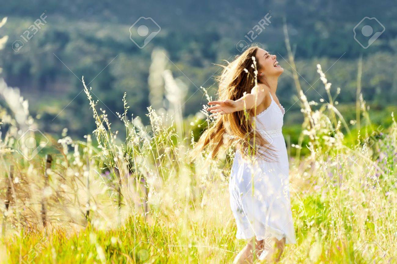 beautiful girl laughs and dances outdoors in a meadow durning sunset - 11474461