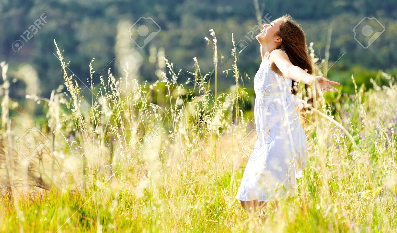 beautiful girl laughs and dances outdoors in a meadow durning sunset - 11474420