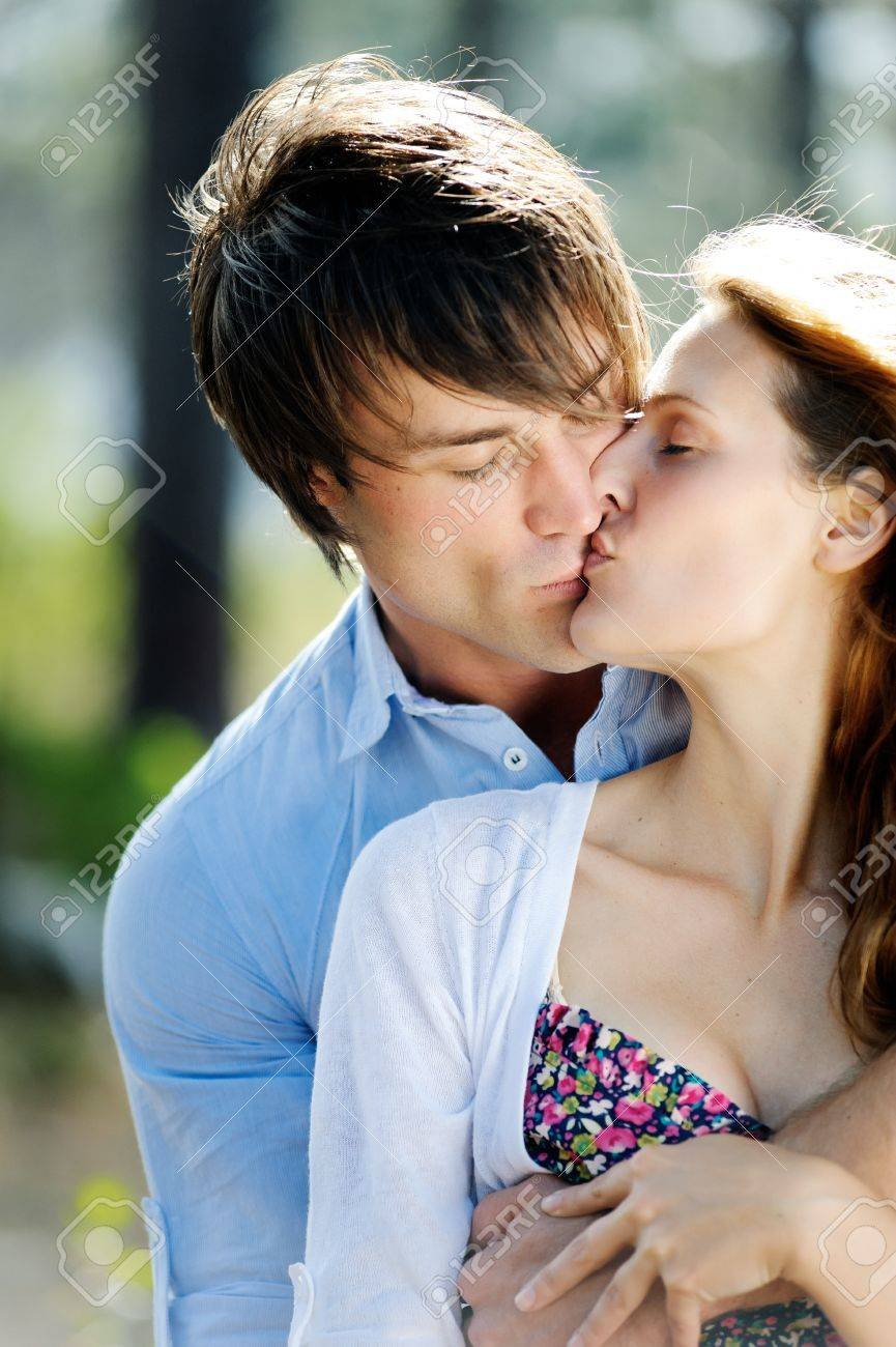 Beautiful young couple kiss outdoors in the forest true love beautiful young couple kiss outdoors in the forest true love and passion stock photo thecheapjerseys Gallery