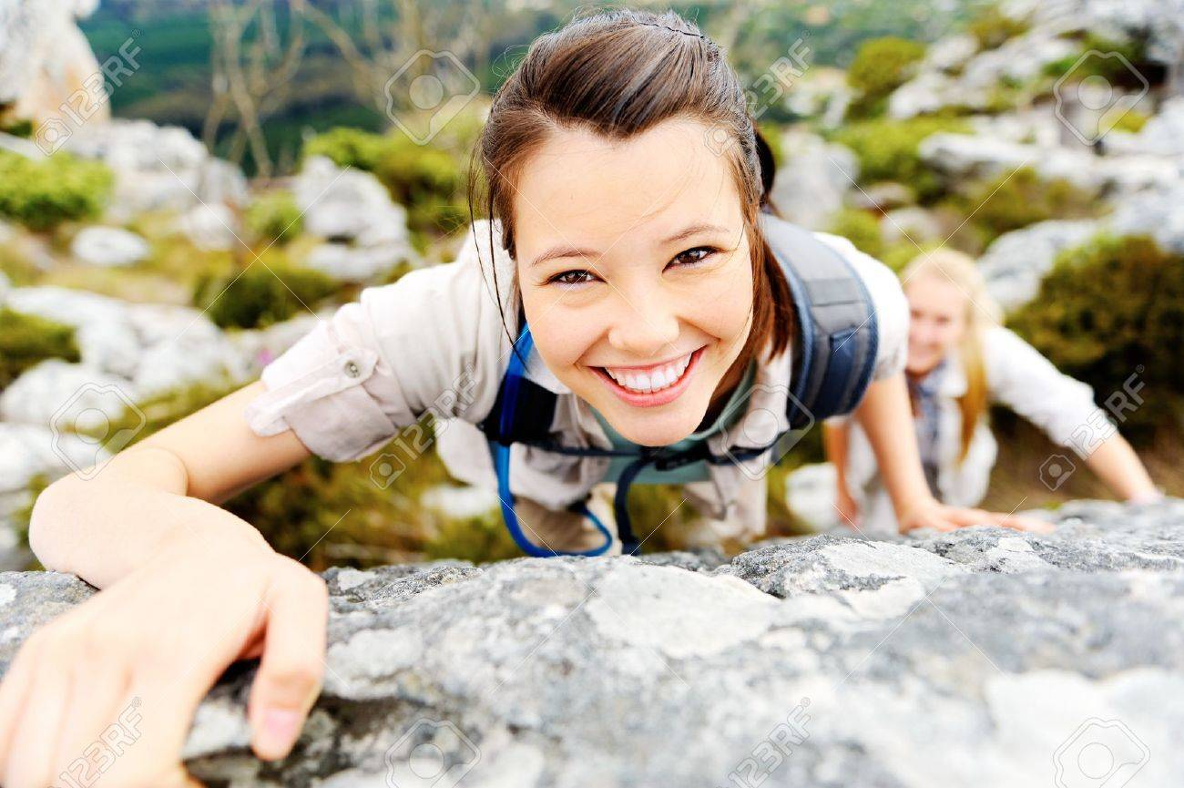 happy carefree hiking backpacker climbs a rock outdoors while leading a healthy lifestyle Stock Photo - 11900159