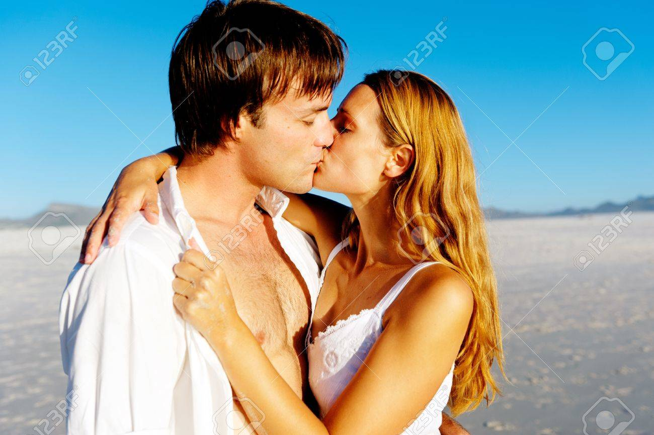 Newlywed couple kissing on honeymoon, beach vacation in summer and an intimate moment. Stock Photo - 12755181