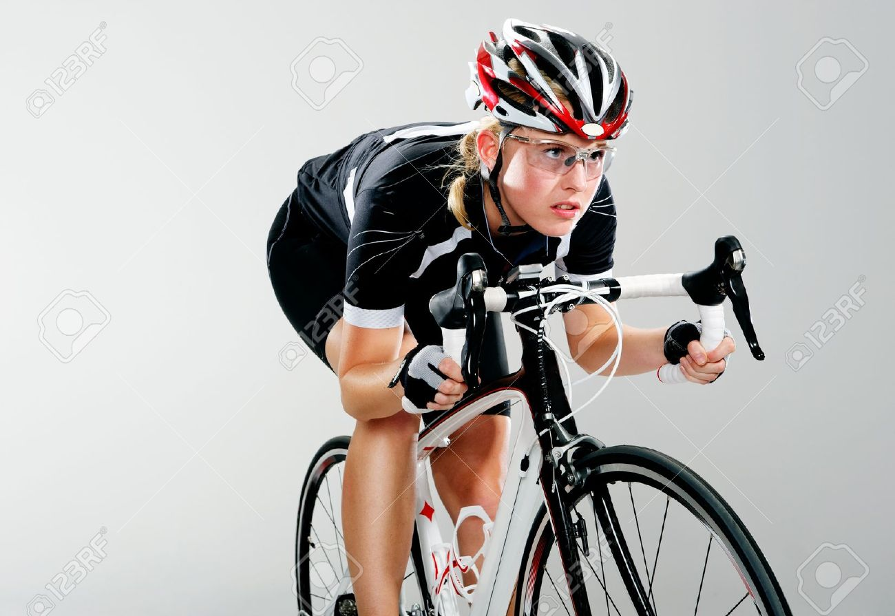 Road bicycle woman riding her bike and concentrating on winning the cycle race. full cycle gear and action as a real cyclist trains for fitness. isolated on grey. Stock Photo - 12755231