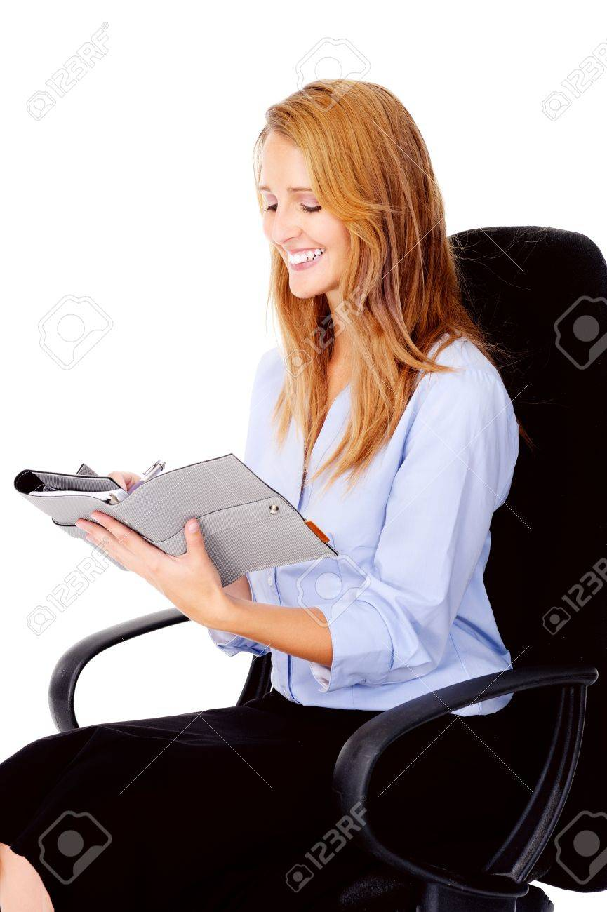 businesswoman writing in her organizer smiling and happy Stock Photo - 13025947