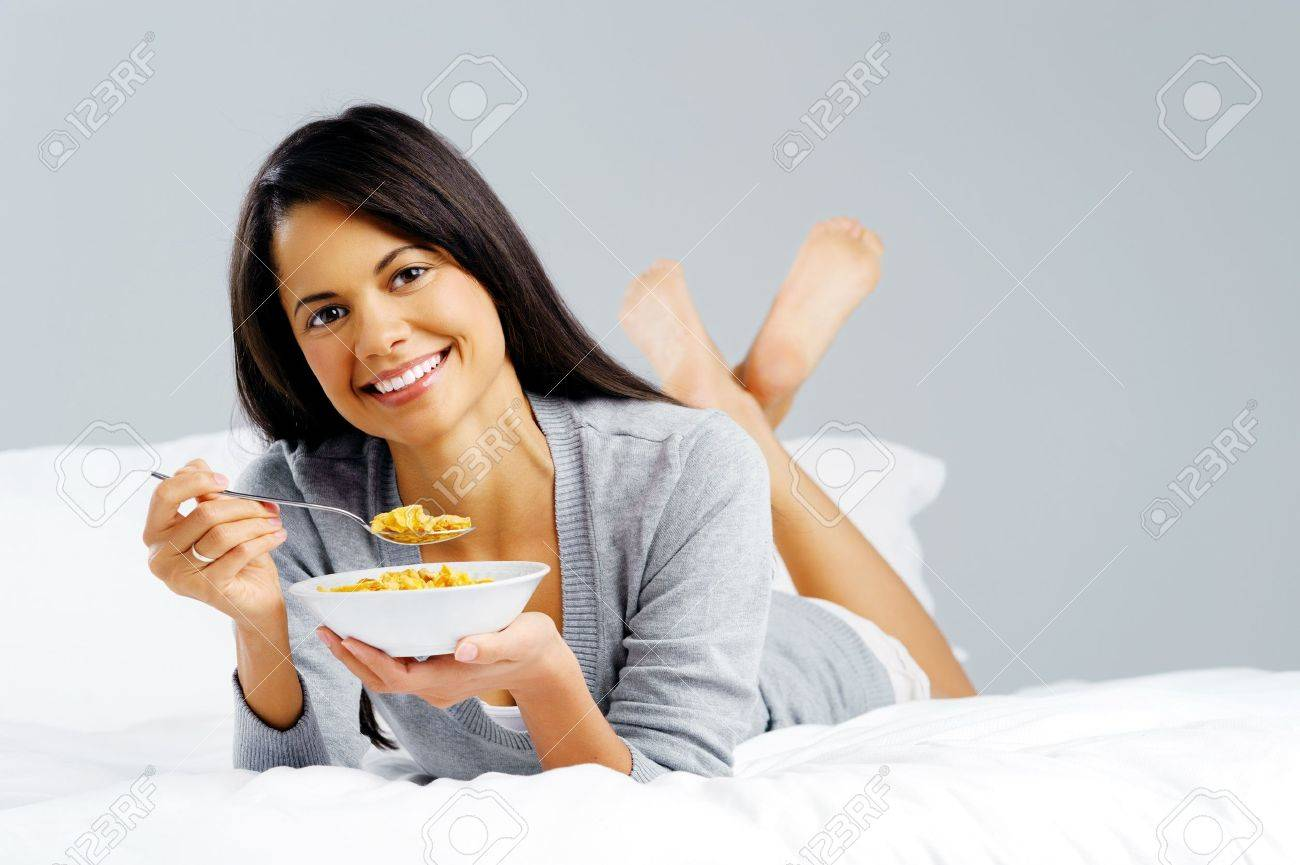 Happy woman with bowl of cornflakes eating breakfast in bed  healthy start to the day Stock Photo - 14182037