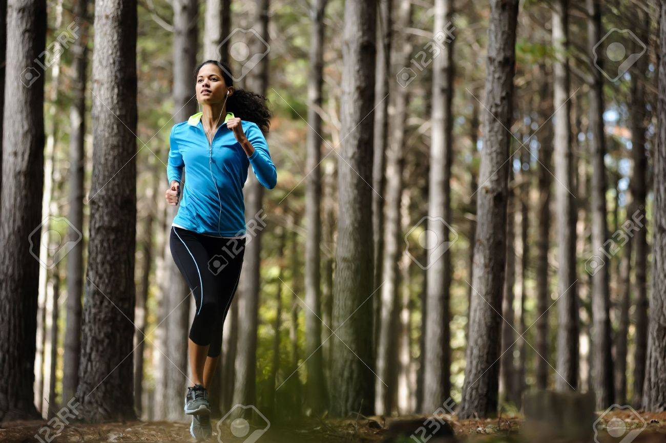Woman running in wooded forest area, training and exercising for trail run marathon endurance  Fitness healthy lifestyle concept Stock Photo - 14342231