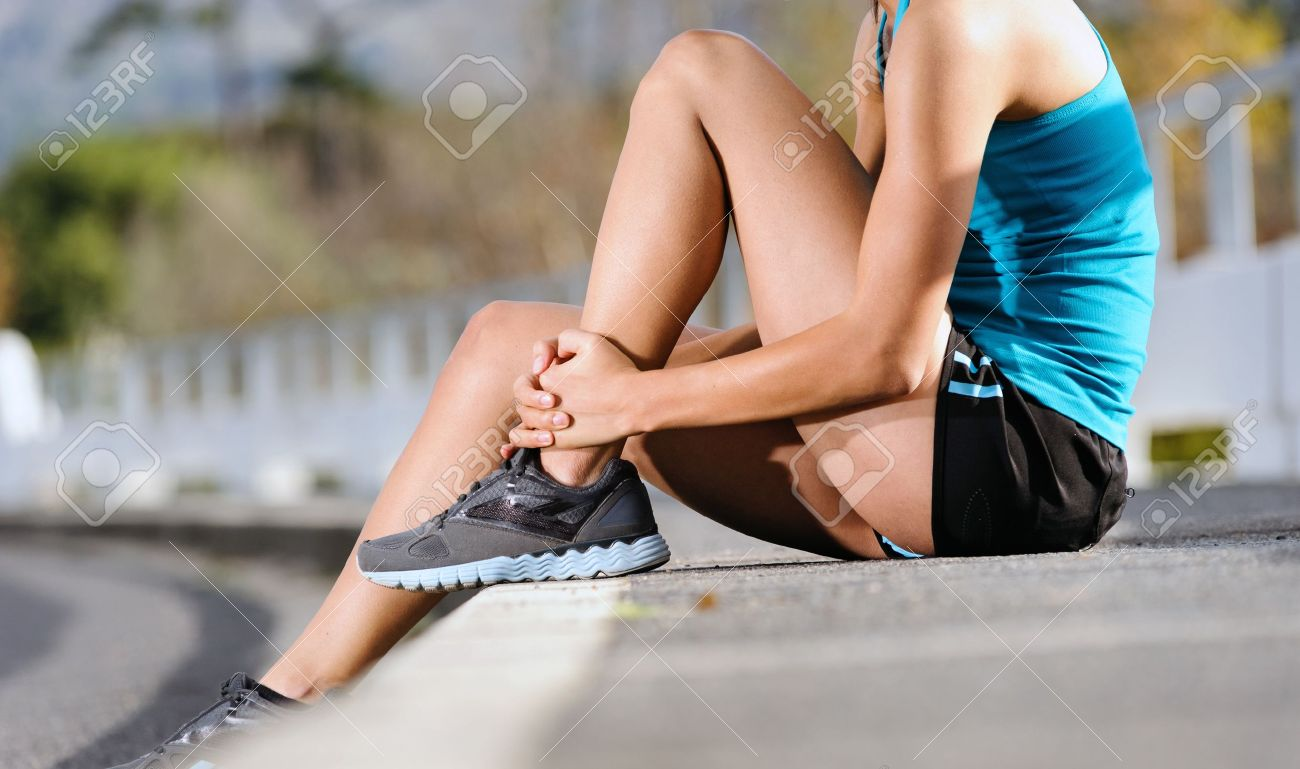 runner with ankle injury holds foot to reduce pain. running problem for athlete training outdoors Stock Photo - 14462745