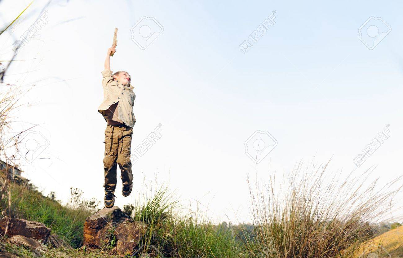 young boy jumping with wooden sword playing pretend explorer outdoors Stock Photo - 14900020