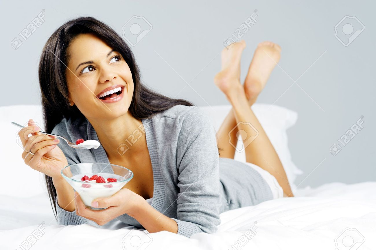 Breakfast woman with yoghurt cereal lying in bed eating a healthy snack with fruit and carefree smile Stock Photo - 14874078