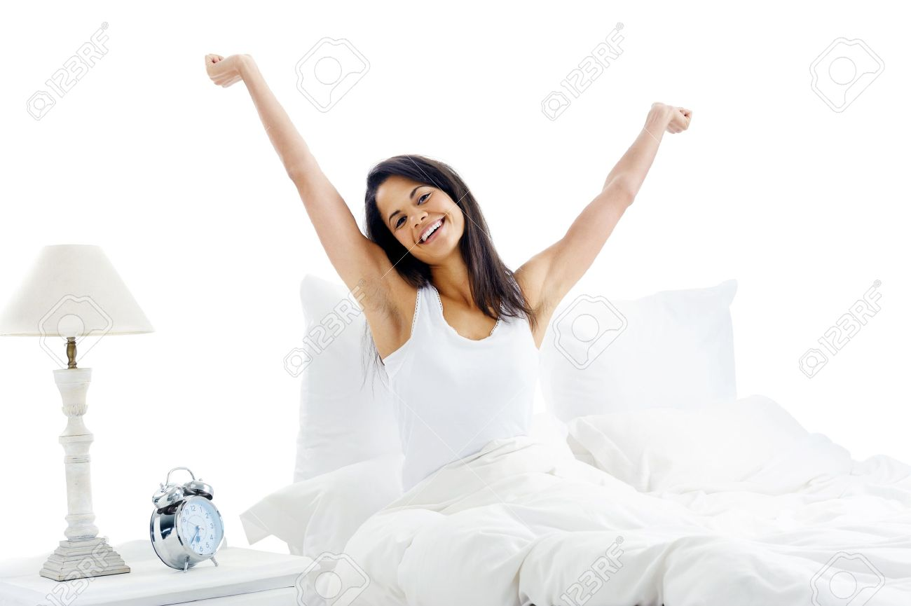 Tired sleepy woman waking up and yawning with a stretch while sitting in bed isolated on white background Stock Photo - 15981300
