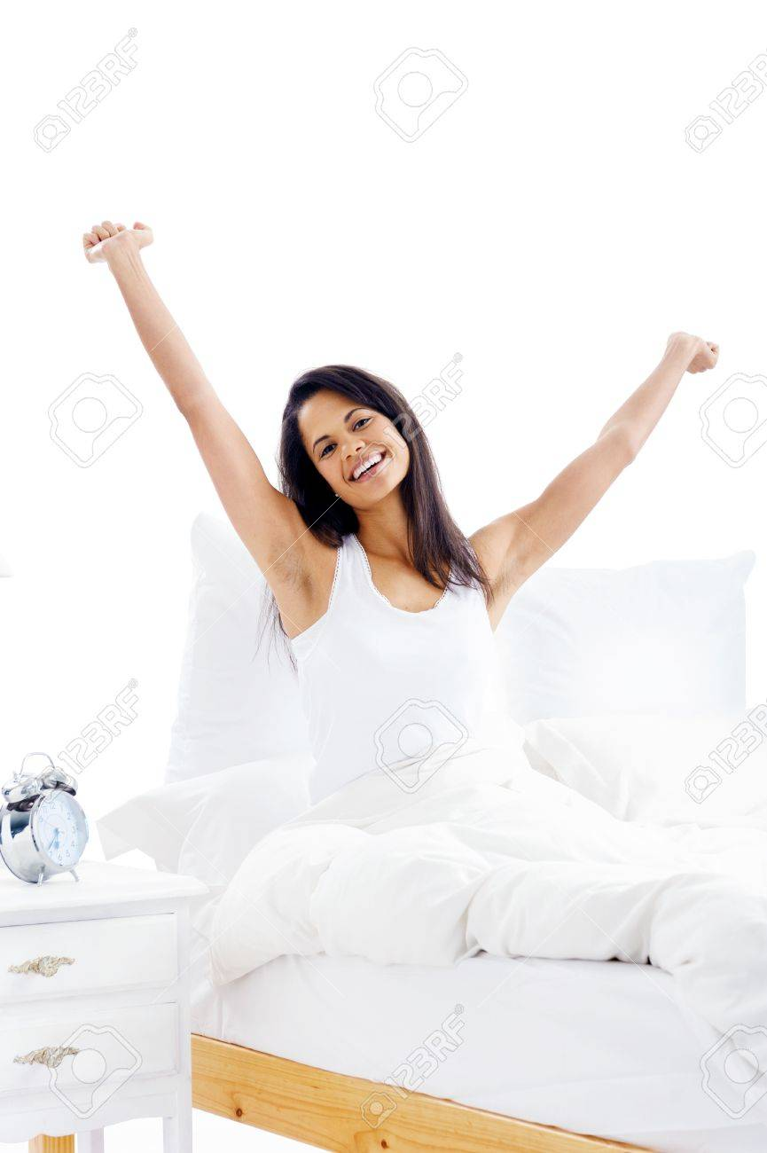Tired sleepy woman waking up and yawning with a stretch while sitting in bed isolated on white background Stock Photo - 15981304