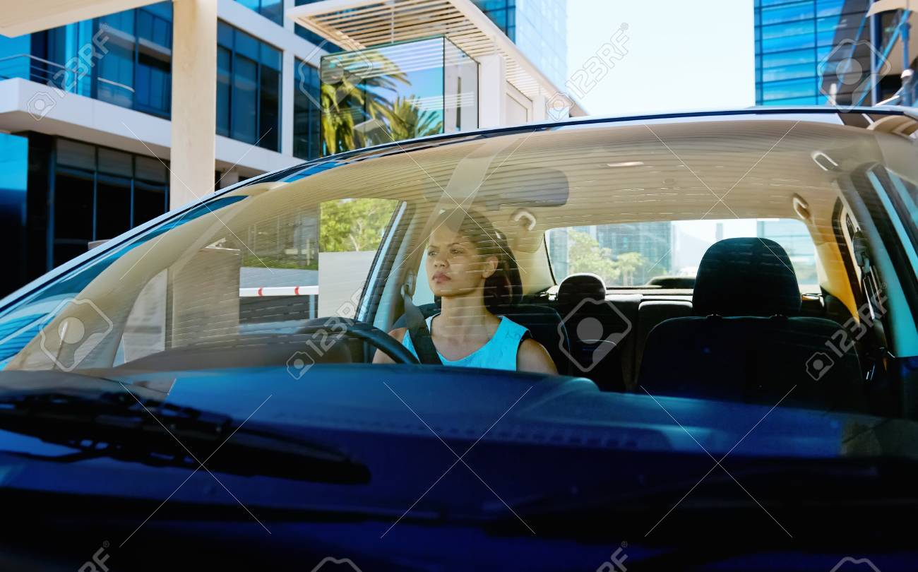 successful businesswoman driving car through modern urban city with reflections of buildings Stock Photo - 17635932