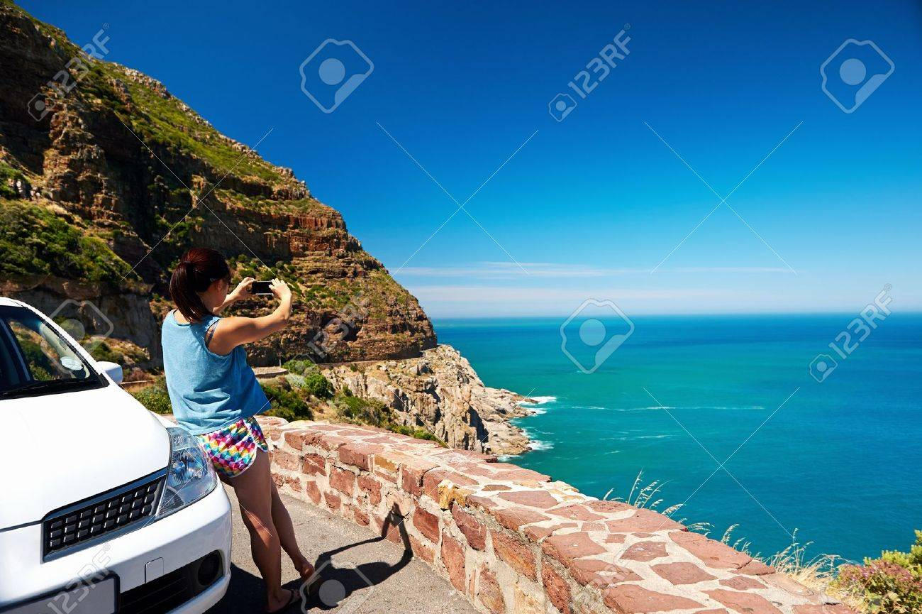 Tourist woman taking a photograph of scenic ocean mountain road chapmans peak in cape town south africa with rental car Stock Photo - 17636192