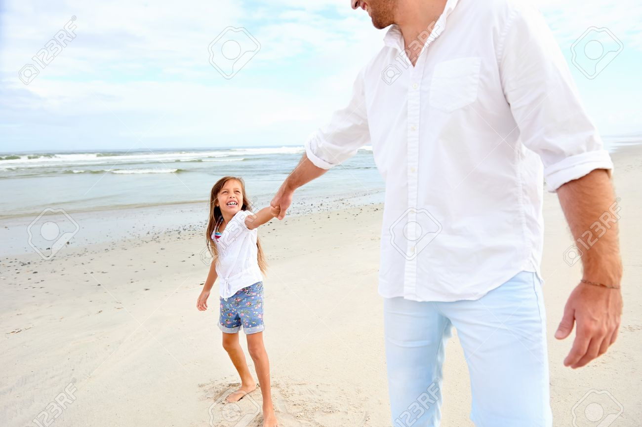 Father And Daughter Holding Hands On The Beach Together Happy