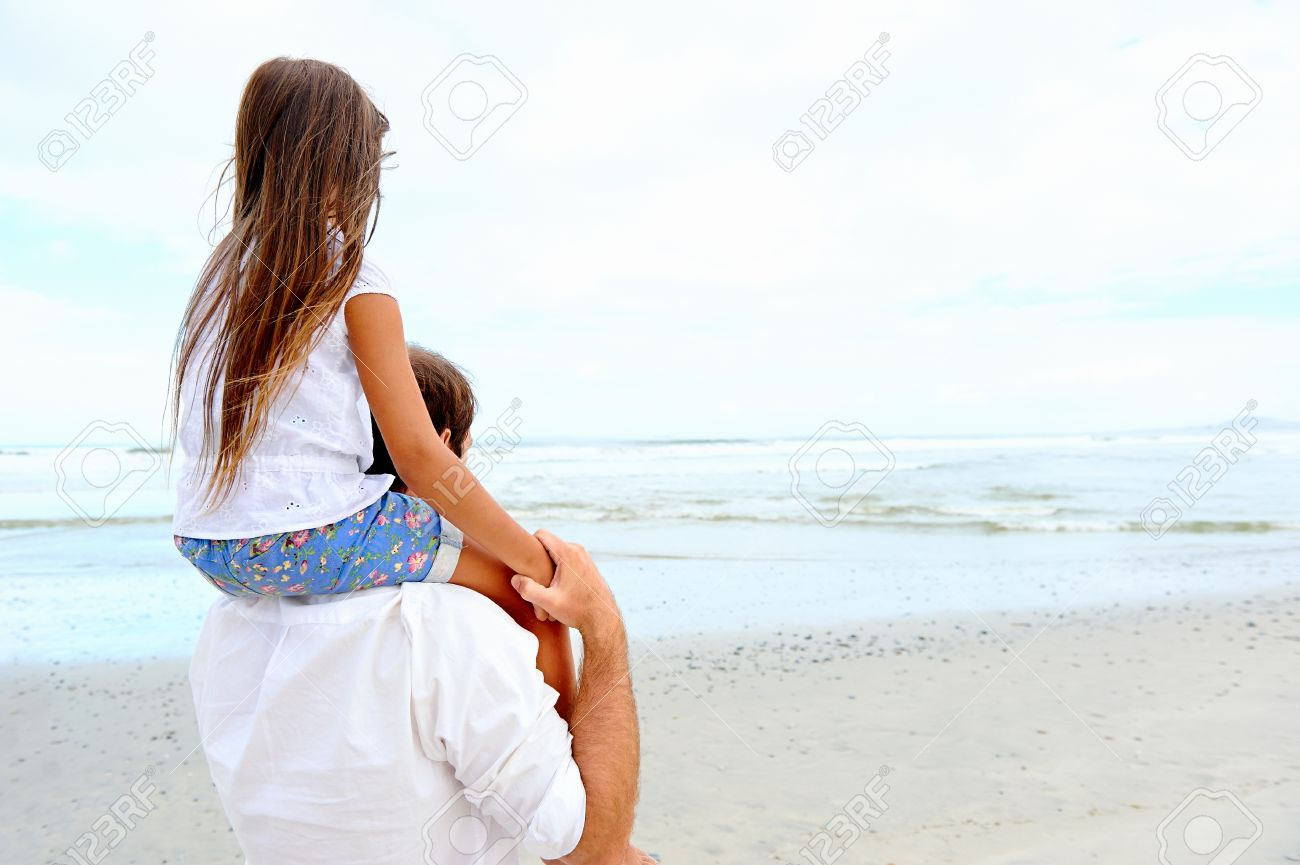 loving father with daughter on shoulders walking on the beach