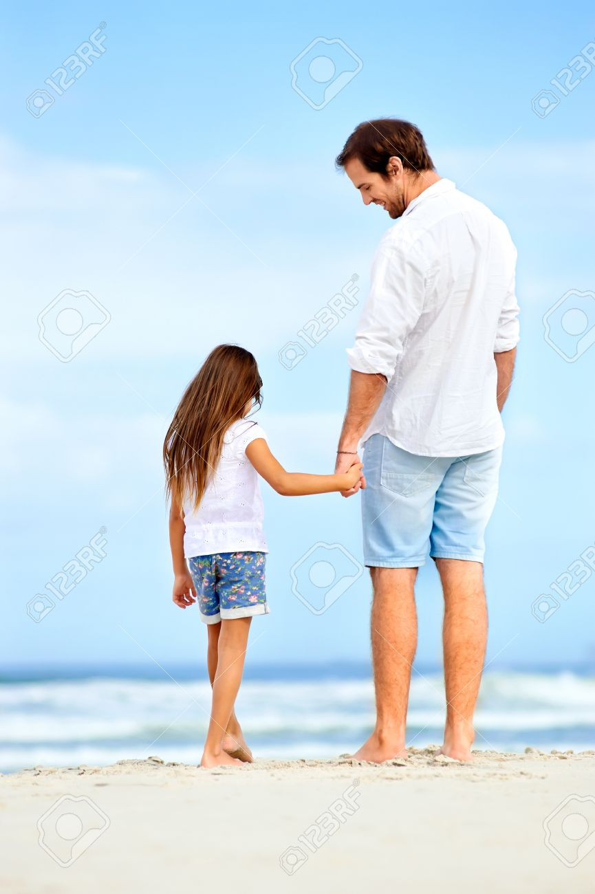 Father and daughter holding hands on the beach together happy and loving vacation Stock Photo - 18787841