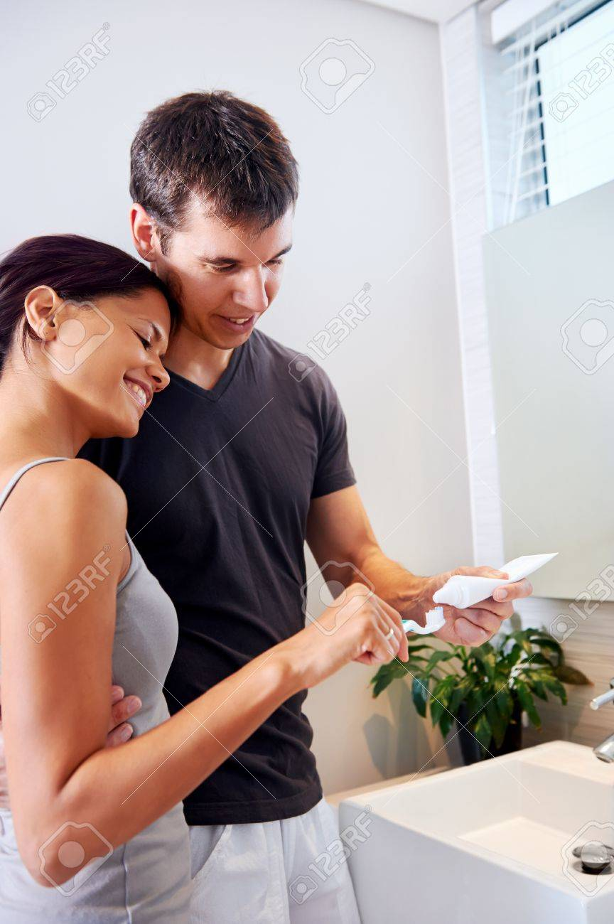 Carefree Real Couple Brushing Teeth In The Bathroom Together Daily Routine Dental Health Stock Photo