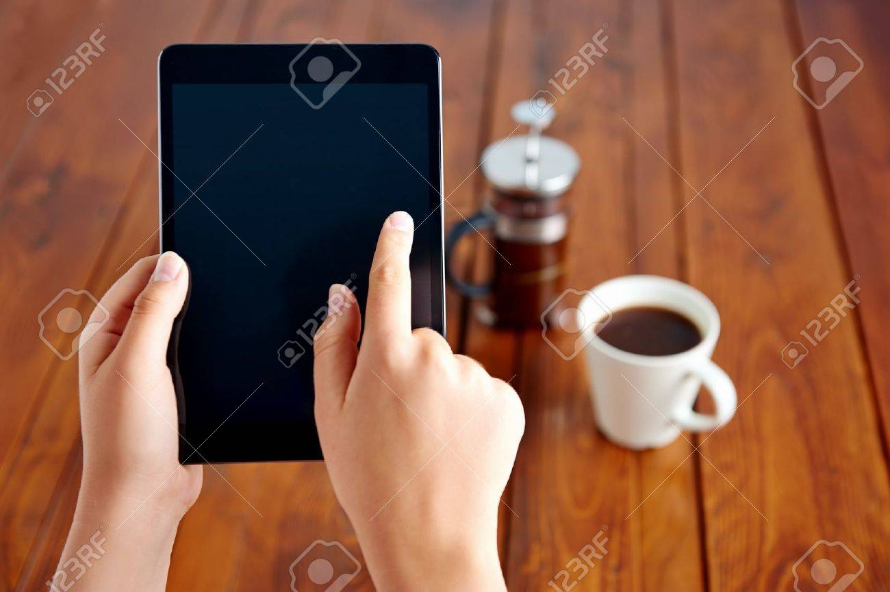 Young woman uses tablet while relaxing at home with coffee on the sofa couch Stock Photo - 19943900