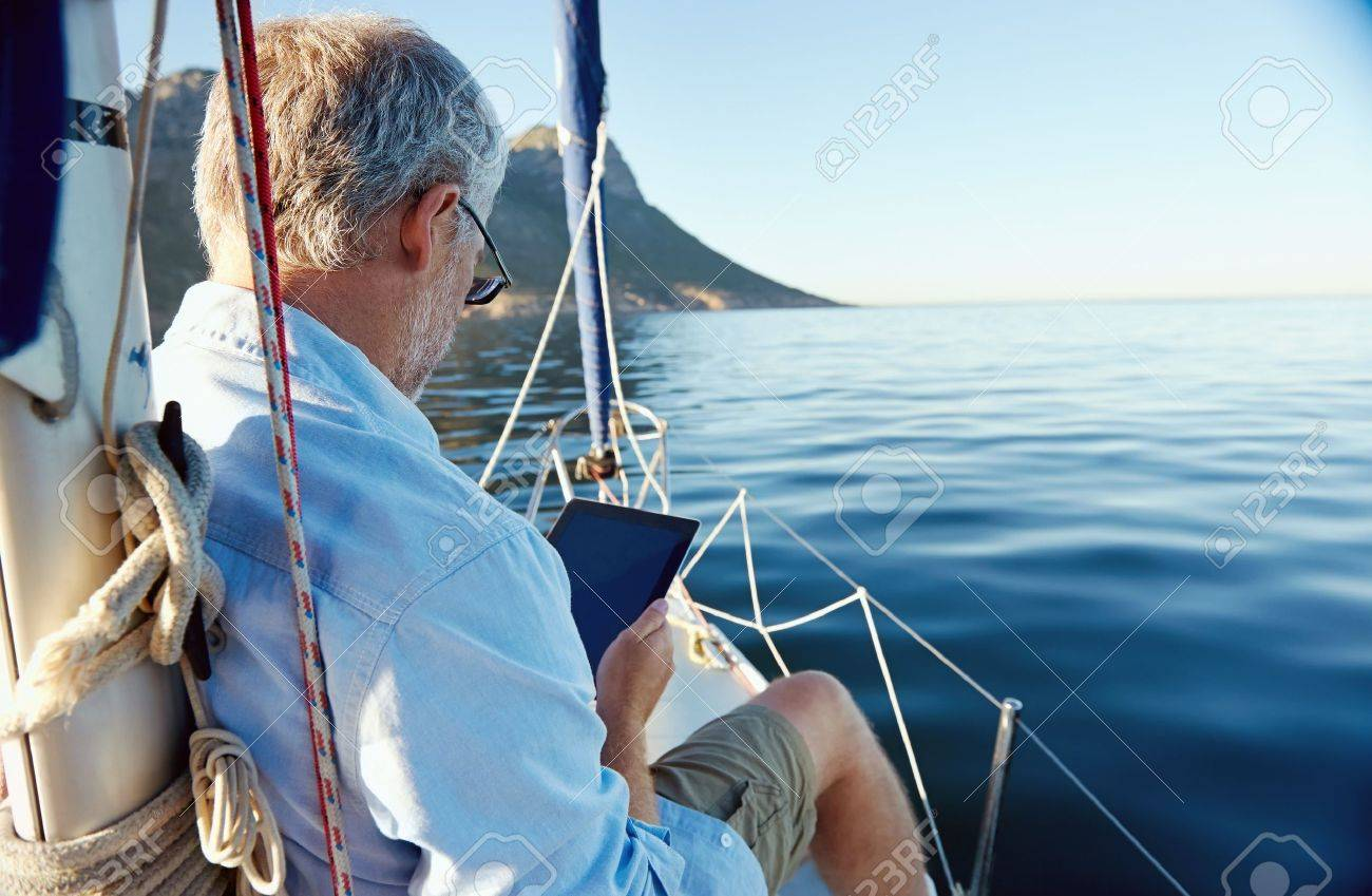 sailing man reading tablet computer on boat with modern technology and carefree retired senior successful lifestyle Stock Photo - 20237578
