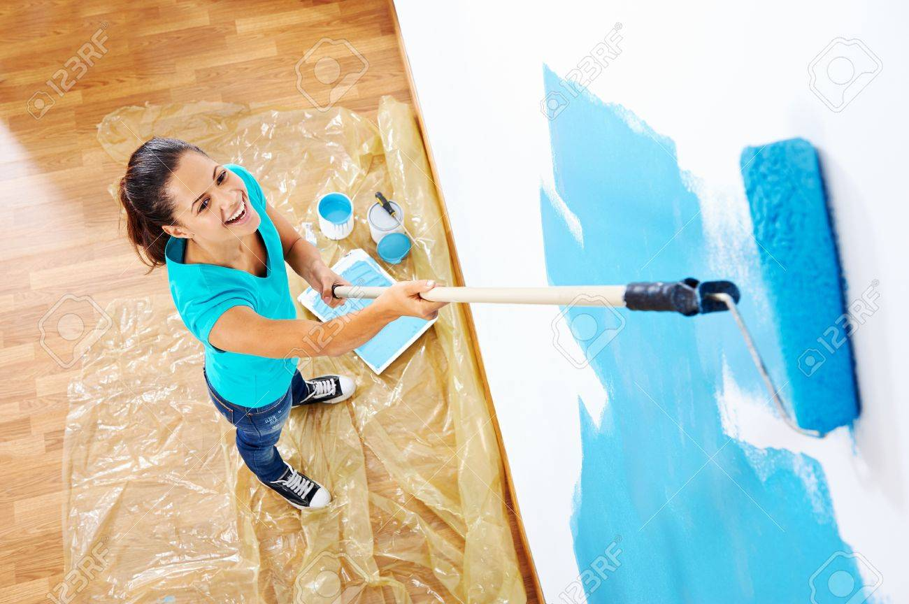 overhead view of woman painging new apartment standing on wooden floor Stock Photo - 20571313