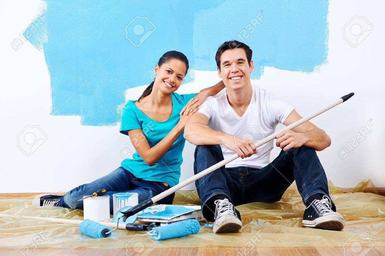 Cute Couple Painting New Home Together Portrait While Sitting On Wooden Floor Stock Photo