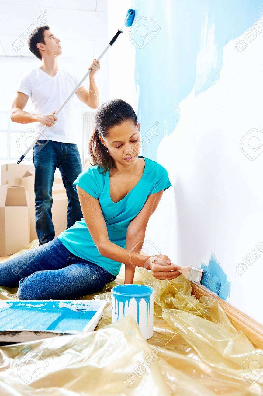 Couple Painting New Home Together With Blue Color Happy And Carefree Relationship Stock Photo