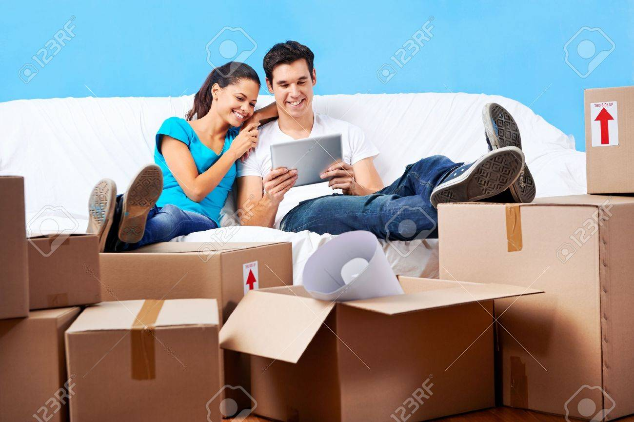 couple moving in together relaxing on sofa couch with laptop tablet computer and boxes Stock Photo - 20571319
