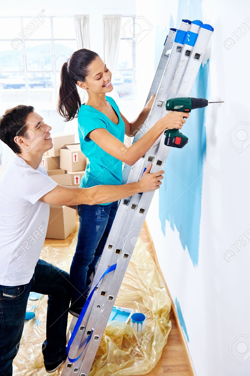 couple drilling in wall doing diy at new home after moving in together Stock Photo - 20761057