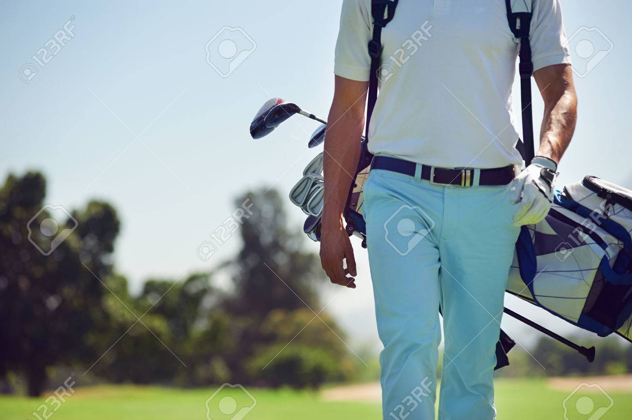 Golf player walking and carrying bag on course during summer game golfing - 24914910