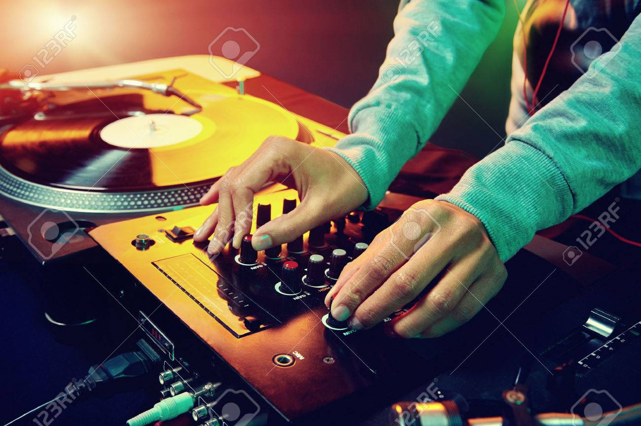 Dj hands on equipment deck and mixer with vinyl record at party Stock Photo - 25018784