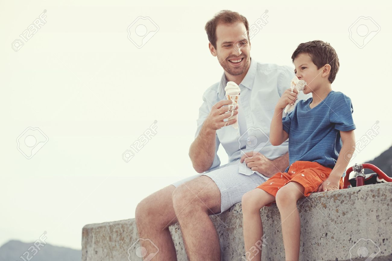 Father and son eating icecream together at the beach on vacation having fun with melting mess Stock Photo - 25281139