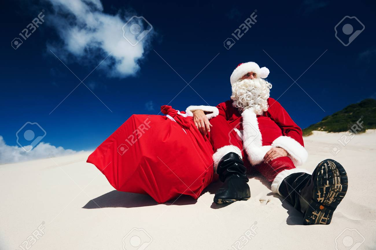 Father Christmas sitting on the beach sand next to his sack of presents Stock Photo - 29194693