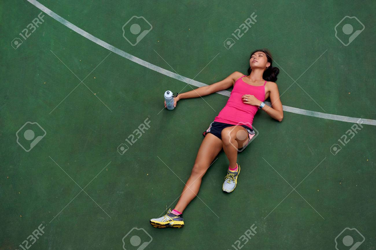 exhausted sporty woman runner laying on basketball court after fitness running workout outdoors - 40834432