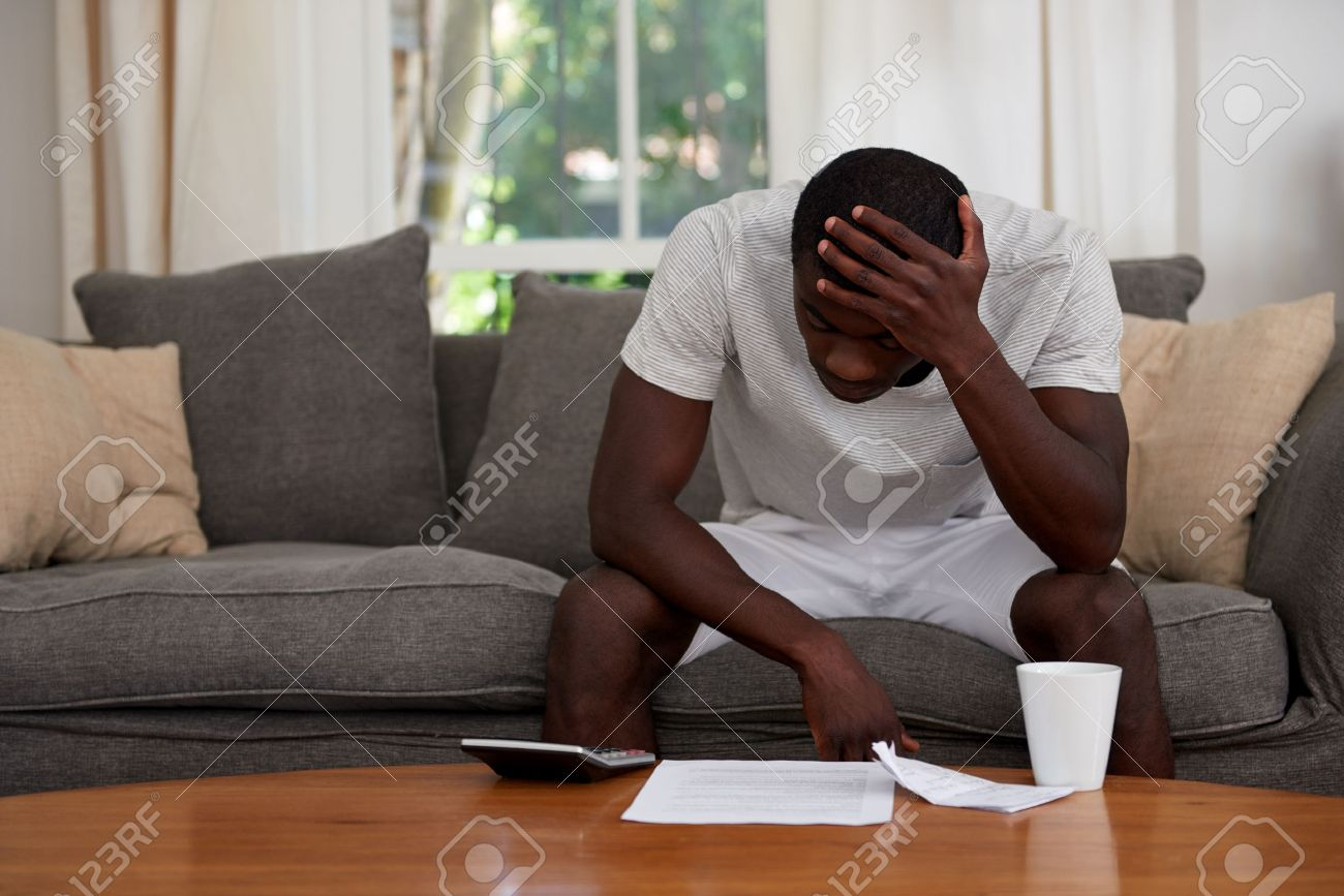 Disapointed Troubled African Black Man Sitting On Sofa Couch Calculating  Home Bill Finance Debt In Living