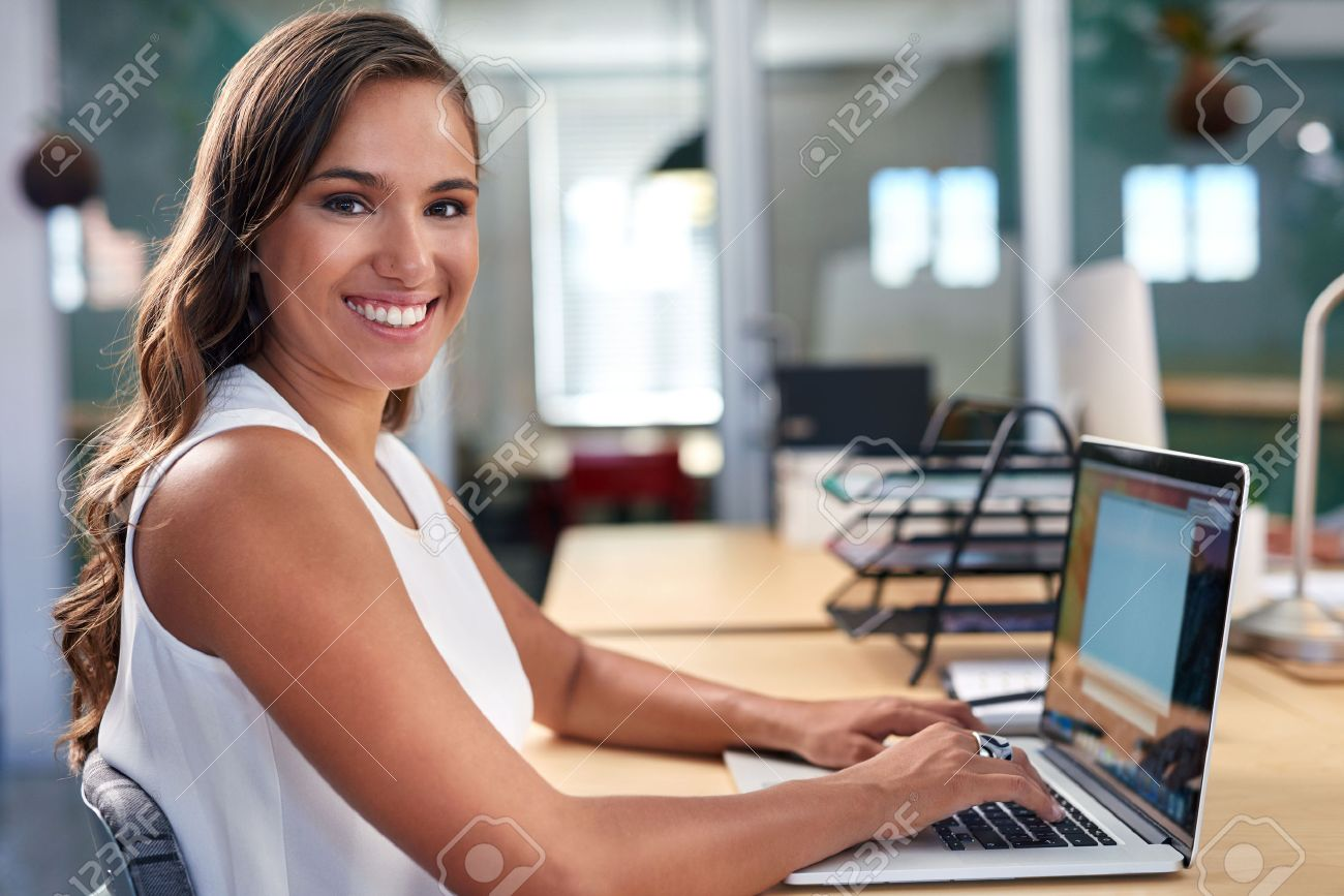 portrait of beautiful young business woman working on laptop computer at office desk Stock Photo - 45973859