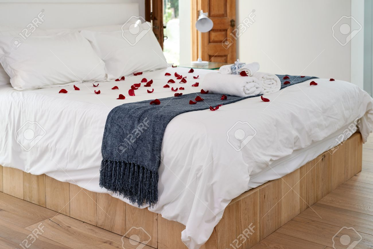 Decorated romantic hotel honeymoon bed with red rose petals and towels. Stock Photo - 49038286