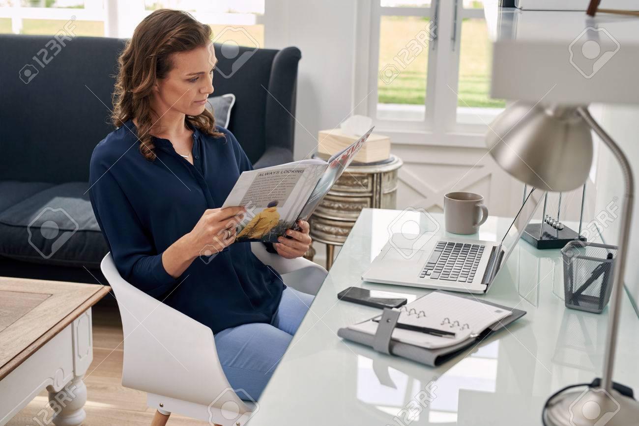 カジュアルな実業家装着自宅オフィス ビジネス雑誌を見て ロイヤリティー