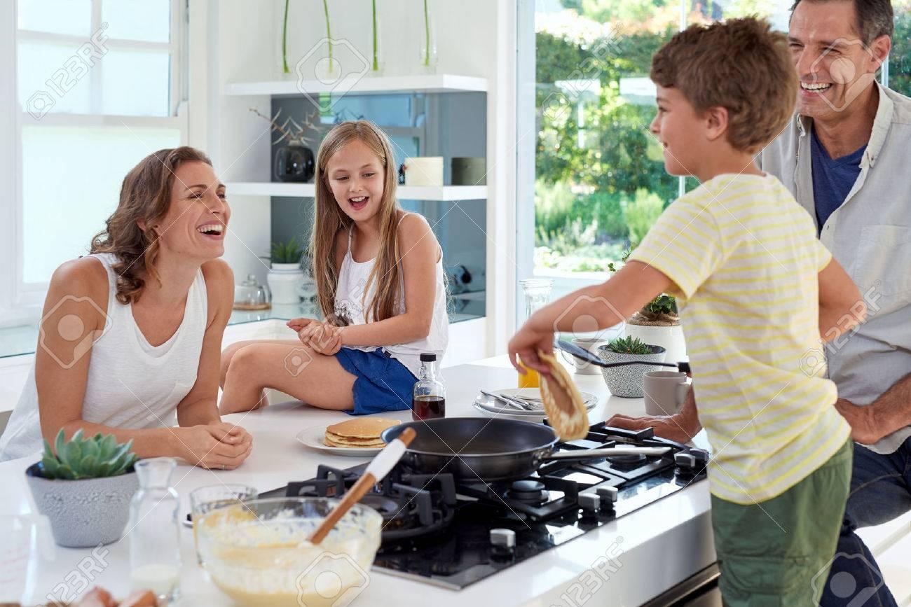 Happy caucasian family standing around stove, son making pancakes on stove - 49223934