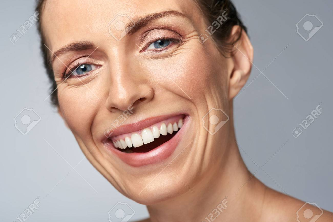 Happy laughing middle age woman in studio, isolated on grey - 57346979