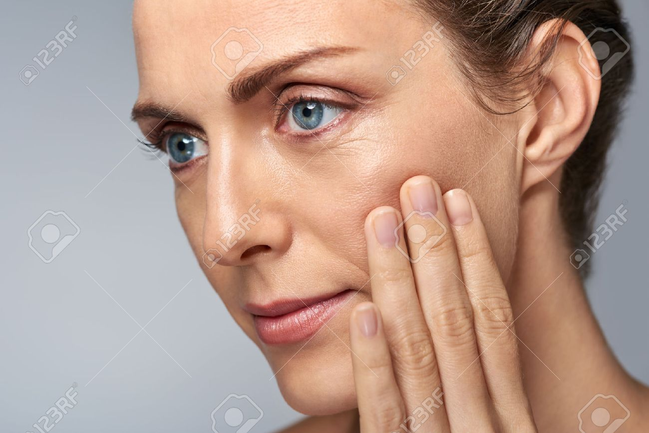 Attractive middle aged woman touching her cheek skin, mature beauty concept - 57346982