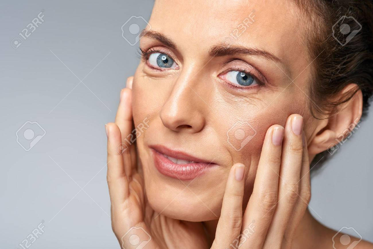 Attractive woman touching her face, mature beauty concept - 57346984