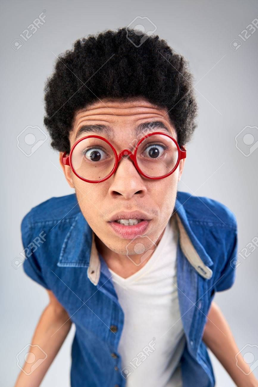 Funny portrait of young man with afro with eyes wide open, shocked facial expression in studio - 61471455